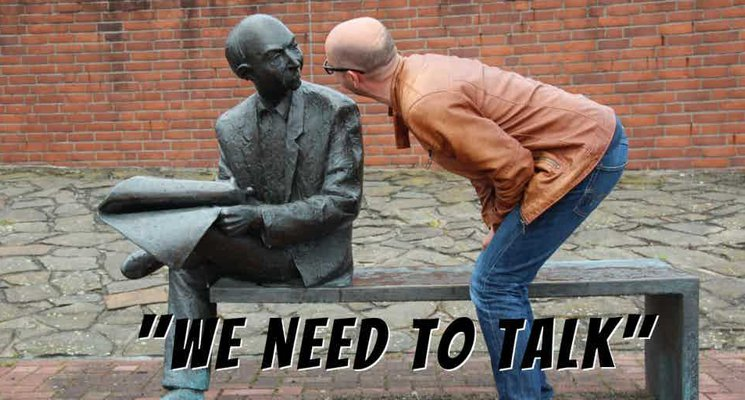"Man bent-over, face-to-face, talking to a statue of a man sitting on a bench. ""We Need to Talk"" text on bottom of image."