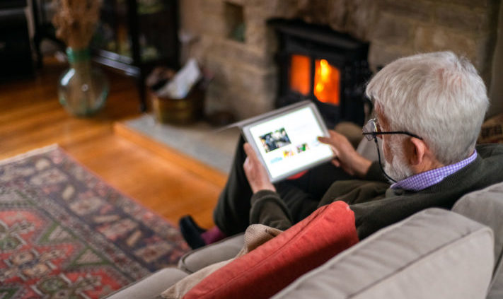 Older man relaxes on sofa by a fire, and looks pictures on his tablet.