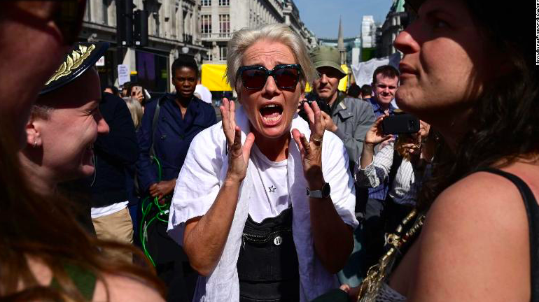 Woman wearing a white T-shirt and wearing sunglasses, shouts during a demonstration on a crowed street.