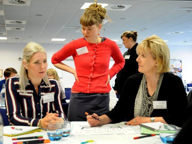 Three women appearing to be problem solving. Two are seated at a table, with paper and markers. One woman is standing. The image title is generations working together.org.