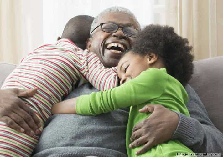 Happy, laughing grandfather, hugging boy and girl