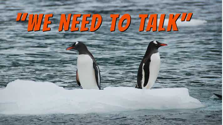 """Two penguins on an ice floe, facing in opposite directions, with a caption that says, """"We Need to Talk"""""""
