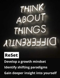 White neon sign on black background with the words, Think About Things Differently. The lettering of differently, is upside down and backward. Other text says ReSet, Develop a growth mindset, Identify shifting paradigms, Gain deeper insight into yourself