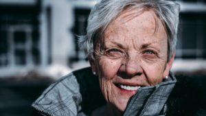 Head shot of fit, smiling older woman wearing grey jacket