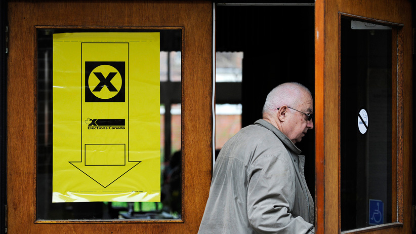 An older male voter enters a polling station for a Federal Election in Toronto